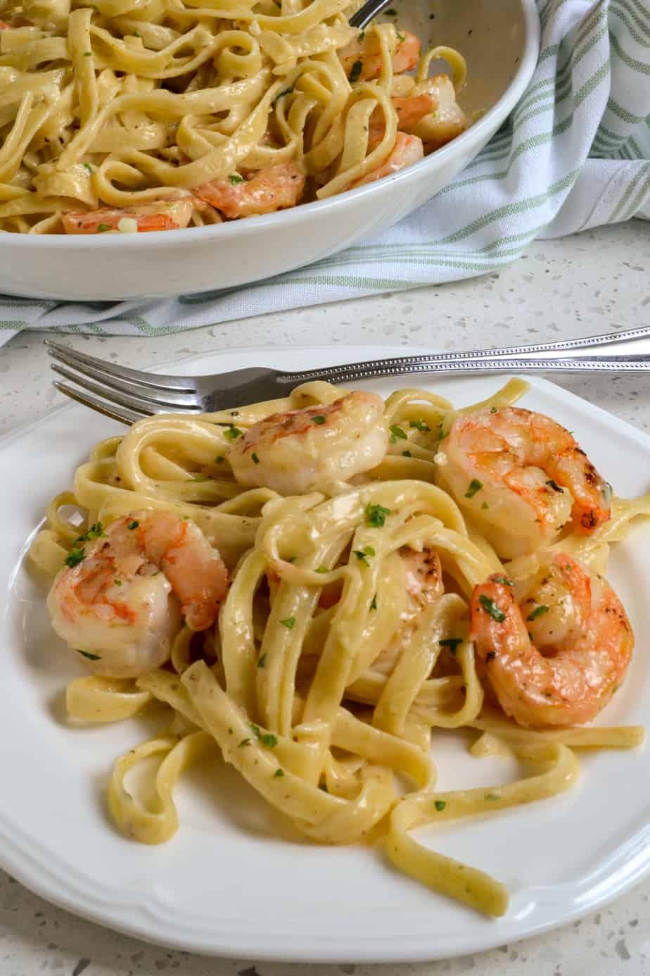 A plate of fettucine alfredo pasta with shrimp