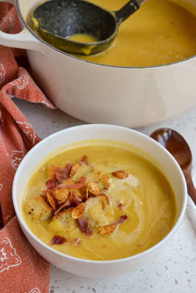 A bowl of homemade pumpkin soup topped with fresh croutons, crisp bacon and pepitas.