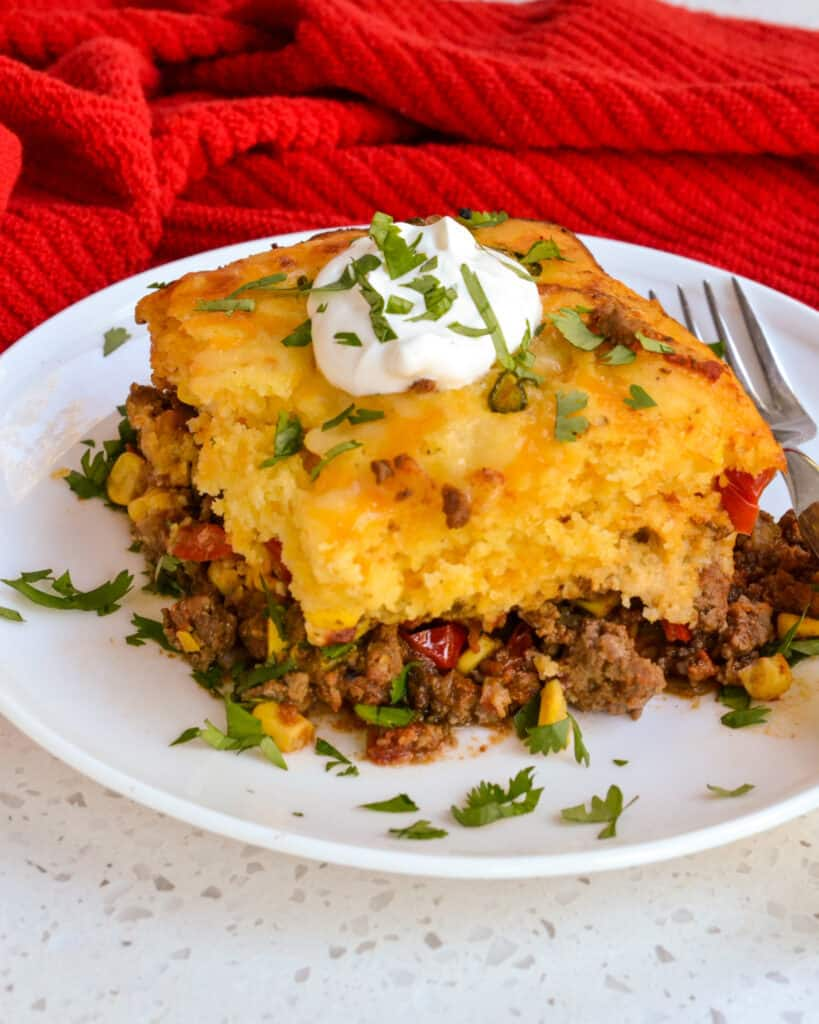 A slice of Tamale Pie with sour cream and chopped cilantro.