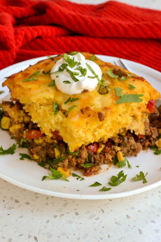 Easy tamale pie with seasoned ground beef, tomatoes, and onions all topped with a cornbread crust.