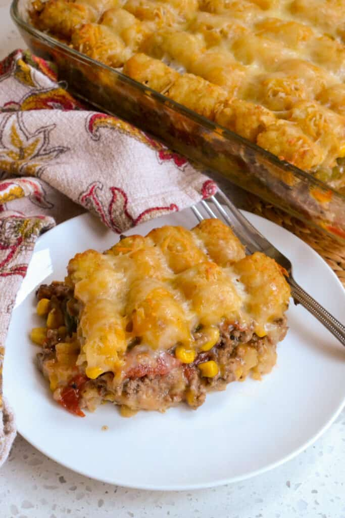 Fun and easy tater tot cowboy casserole with ground beef, cheese, green beans, tomatoes, and corn.