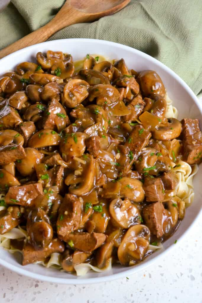 Beef with mushrooms and gravy over noodles.