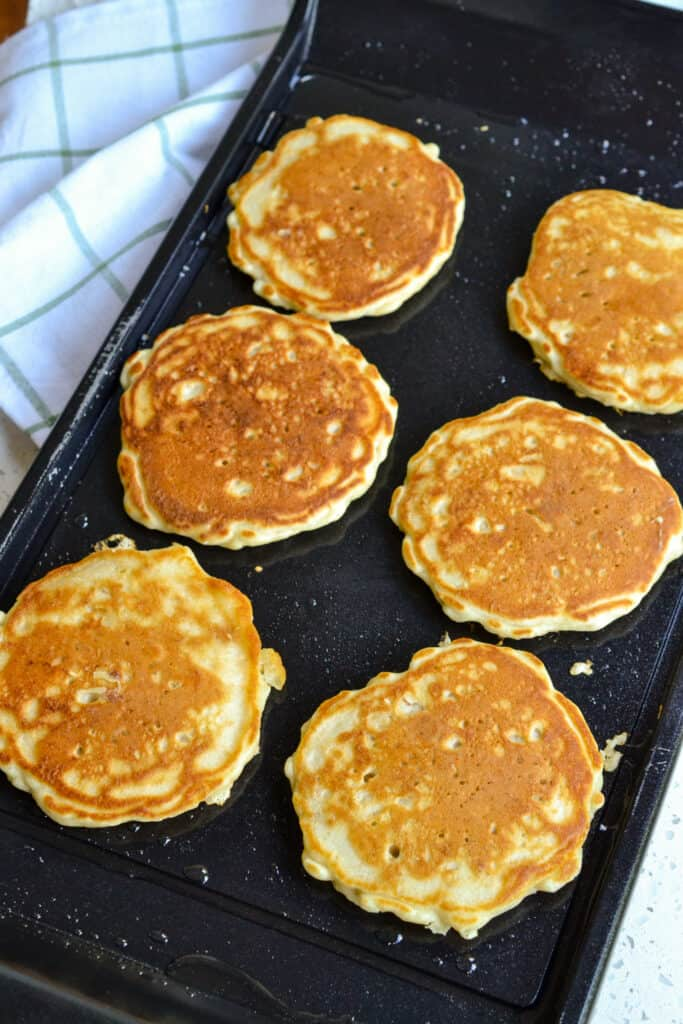 Oatmeal pancakes on a griddle.
