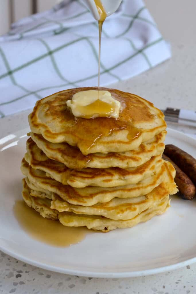 A stack of oatmeal pancakes with butter and syrup.