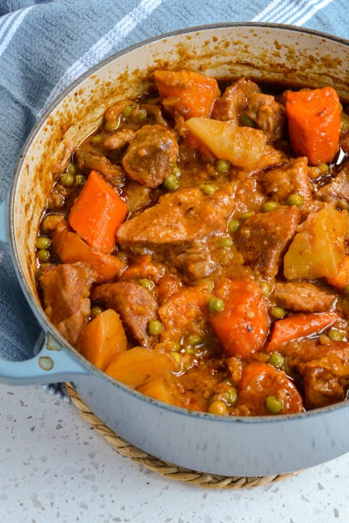 A Dutch oven full of pork stew with carrots, potatoes, sweet potatoes, and peas.